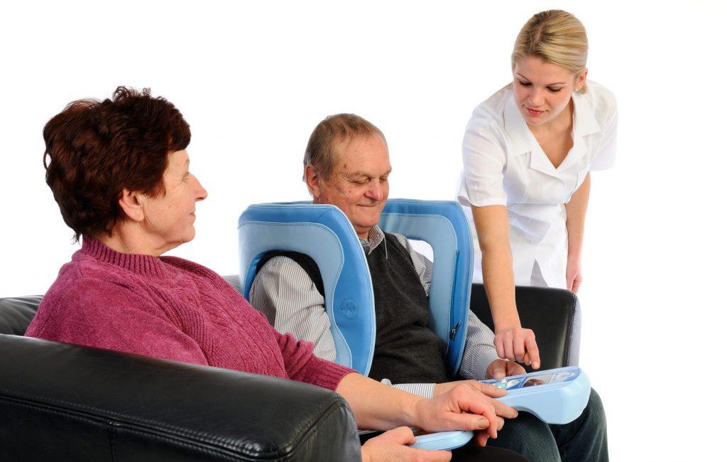 Enfermera ayudando a matrimonio a utilizar la magnetoterapia Biomag